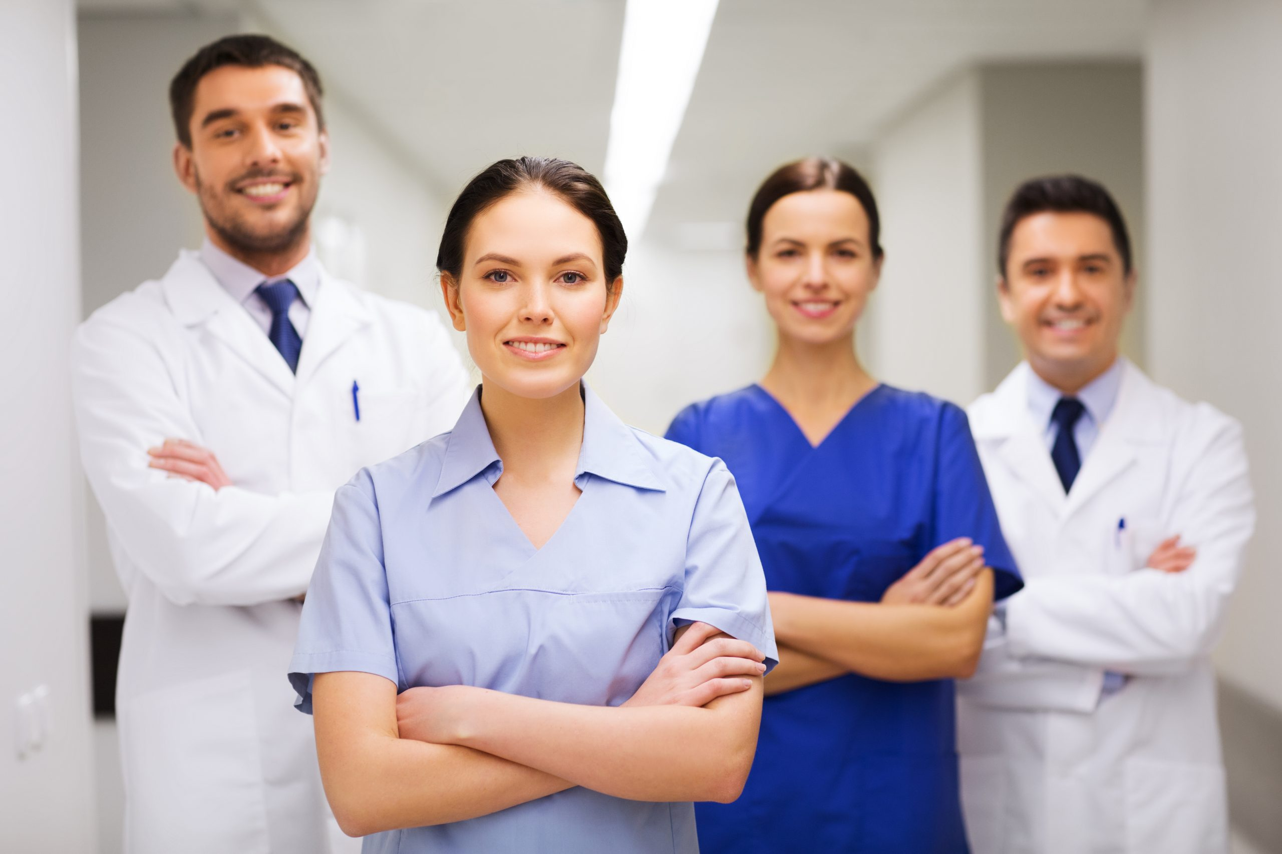 clinic, profession, people, health care and medicine concept - happy group of medics or doctors at hospital corridor